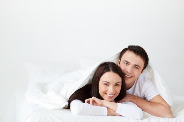 sourire-couple-allonge-dans-son-lit_1098-3788
